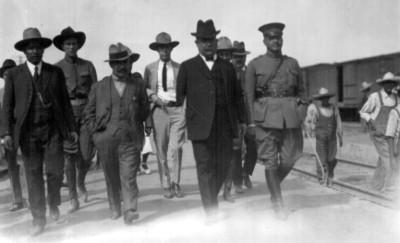 Alvaro Obregón y comitiva caminan junto a vía férrea