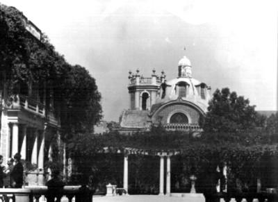 Casa de estilo francés y cúpula de iglesia, vista parcial