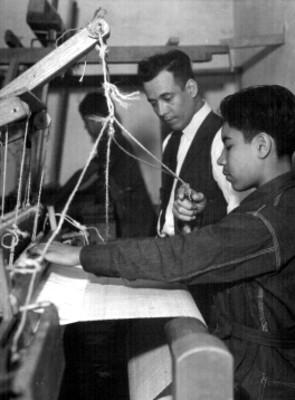 Niños trabajan acompañados de su maestro en el taller con telar