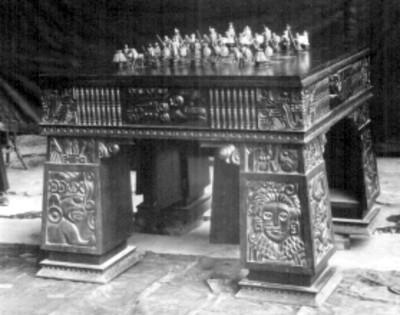 Ajedrez de plata colocado sobre una mesa tallada con diseños prehispánicos