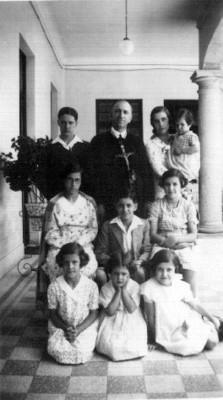 Familia reunida en el portico de una casa, retrato de grupo