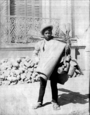 Adolecente vende artesanías de palma en la vía publica