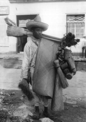 Vendedor de escobas y petates sobre una calle, reprografía