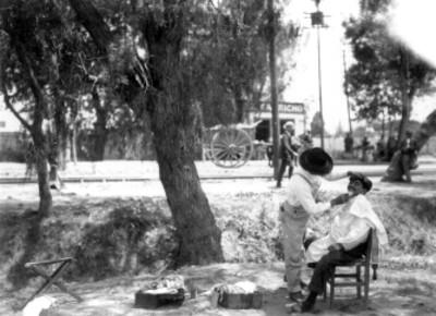 Peluquero rasura a un hombre en un parque, reprografía