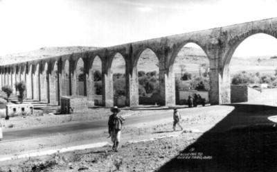 Hombres transitan bajo el acueducto de Querétaro