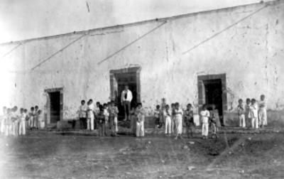 Niños y profesor frente a un salón de clases de la escuela de Tianguistengo
