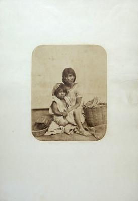 Mujer con su hijo en brazos y canasta de pan a un costado