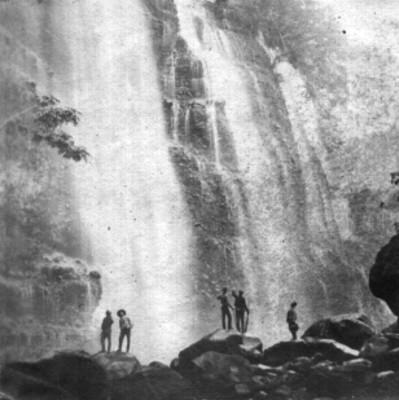 Hombres al pie de una cascada