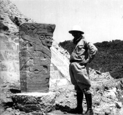 Hombre de pie junto a la escultura del Dios Tajín