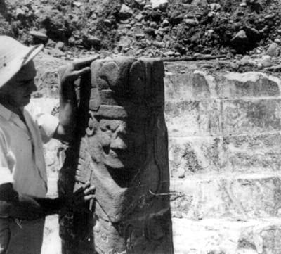 Hombre observa escultura del Dios Tajín