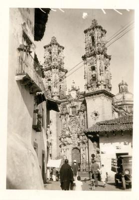Gente camina en las afueras de la Parroquia de Santa Prisca