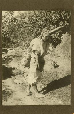Indígena cargando un odre en la espalda, mientras camina por un paraje