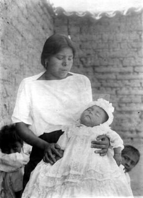 Mujer Nahua cargando a su bebé en patios de una vivienda, retrato
