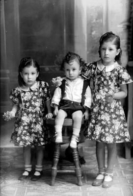 Dos niñas con vestido floreado y niño, retrato de grupo