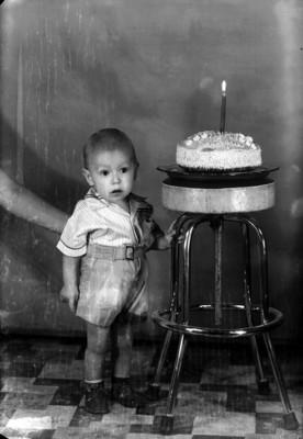 Niño de clase media junto a pastel de cumpleaños