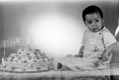 Niño de clase media ante pastel de cumpleaños, retrato