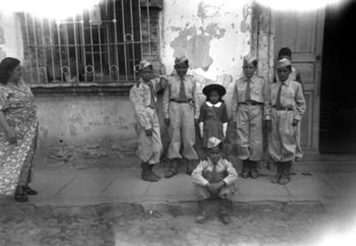 Niños con uniforme militar acompañados de niña en una calle, retrato