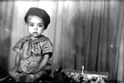 Niño sentado junto a un pastel