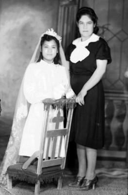 Mujer y niña en reclinatorio con ropa de primera comunión