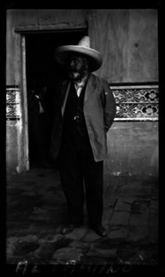 Abraham González de pie junto a una puerta de un edificio, retrato