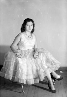 Mujer con vestido de olanes sentada con la pierna cruzada, retrato