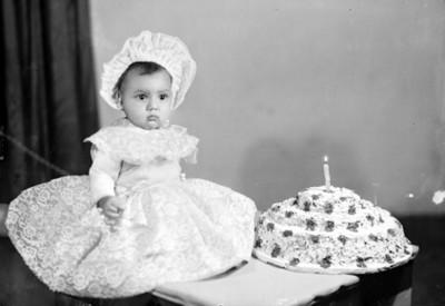 Niña vestida elegantemente sentada junto a pastel de cumpleaños, retrato