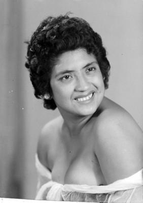 Mujer sonriente y con vestido de hombros descubiertos, retrato