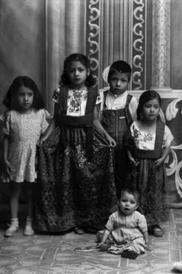 Dos niñas vestidas de chinas poblanas acopañadas por otros 3 niños, retrato