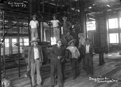 """Trabajadores sobre y junto a una máquina en el """"Ingenio de Zacatepec"""", retraro de grupo"""