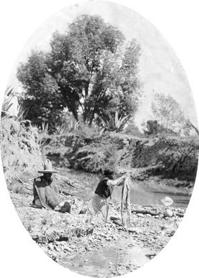 Hombre observa a mujer lavar a orillas de un río