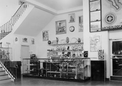 Vista de vitrina con artículos de venta, pinturas y mapa de zonas arqueológicas