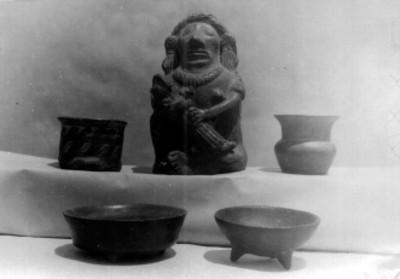 Figura antropomorfa y vasijas prehispánicas, exhibidas en un museo