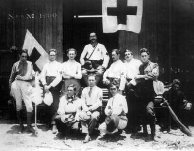 Miembros de la Cruz Roja, frente a vagón de tren, retrato de grupo