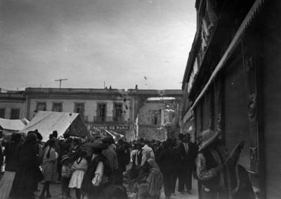 Gente en un tianguis junto a edificios dañados por las descargas de artillería