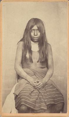 Niña sentada con indumentaria indígena