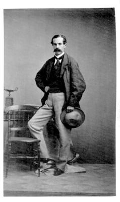 Hombre de pie y con sombrero junto a una silla, tarjeta de visita