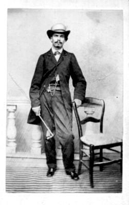 Hombre con sombrero junto a una silla, tarjeta de visita