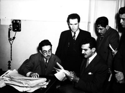 Alfredo Kawaje Ramia, periodista, con abogados y periodistas revisando documentos en una oficina