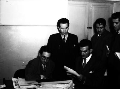 Alfredo Kawaje Ramia, periodista, con abogados revisa periódicos y documentos en una oficina