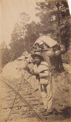 Ollero carga vasijas de barro a la orilla de vías férreas