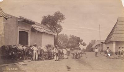"""Arrieros con """"burros"""" en un poblado"""