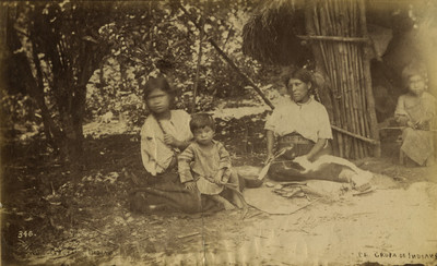 """Mujeres y niños sentados afuera de una choza, """"106. Grupa de indians"""" [sic]"""