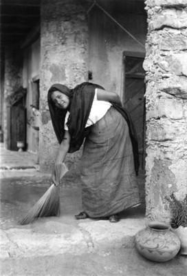 Mujer joven con traje regional y escoba de pasto, retrato