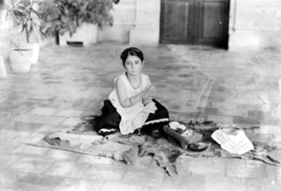 Niña tehuana frente a metate en el piso preparando gorditas, retrato