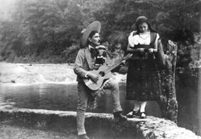 Hombre tocando guitarra ante una mujer