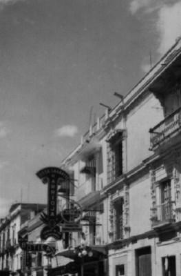 Gente en tianguis y vista lateral de la Iglesia de Santa Prisca