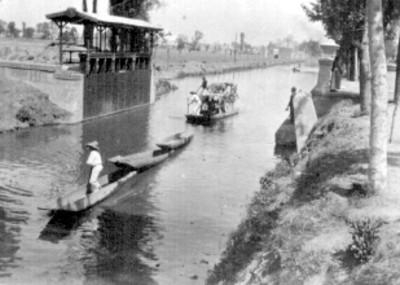 Hombres en canoas transitan por un canal de Xochimilco