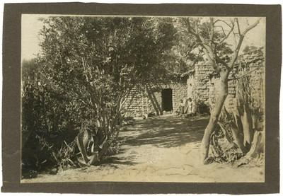 Niñas indígenas afuera de una casa de adobe, retrato