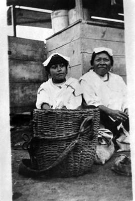 Mujeres indígenas sentadas frente a una canasta