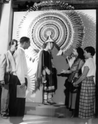 Grupo de visitantes observan un traje típico de la danza de las Guaguas